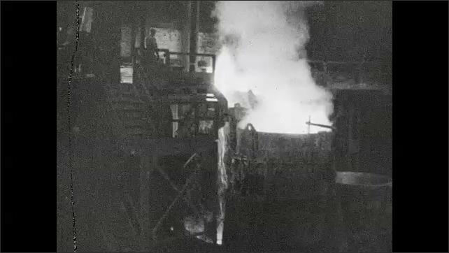 1930s: Factory interior, molten metal pouring into vat, men throw material into vat.