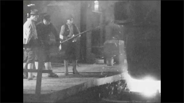 1930s: Molten metal pours from vat in factory, men watching on platform. Man throws ore into metal. Man pulls molten metal from vat.