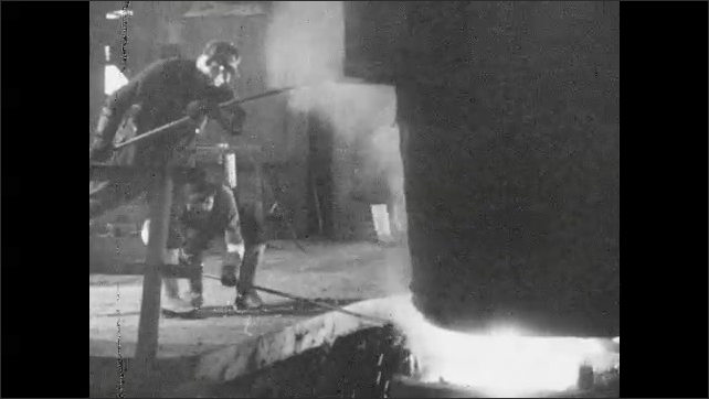 1930s: Men working in factory, pouring molten metal from vat.