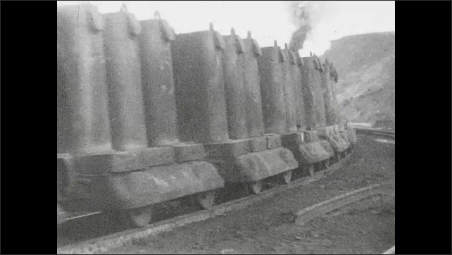 1930s: Train pushes cars carrying steel.