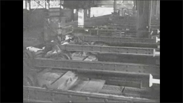 1930s: Mechanical arm moves steel bar from oven. Mechanical arms moving steel in factory. Arm places steel bar in cart.