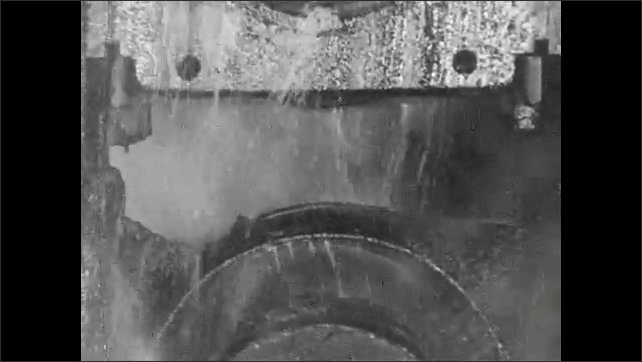 1930s: Close up, steel beam moving through machine, water pouring on machine.