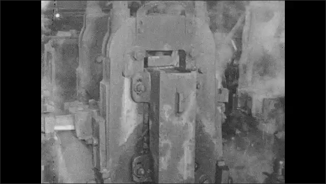 1930s: Steel bar slides down machine in factory. Views of bar moving through machinery.