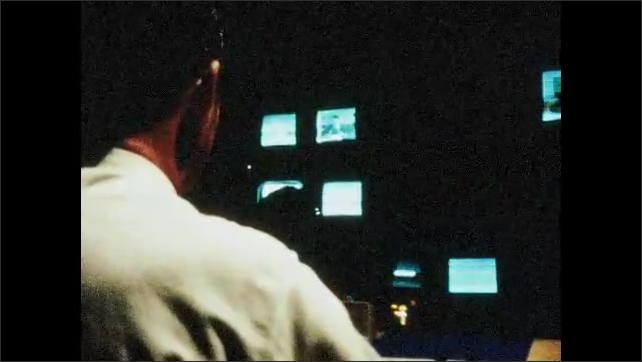 1970s: UNITED STATES: man monitors recording and angles. Man speaks to presenters through earpieces.