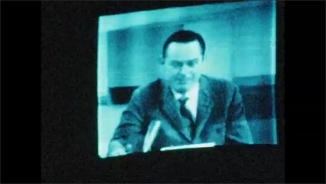 1970s: UNITED STATES: live broadcast. Man on television monitor. Man watches cameras from behind set.