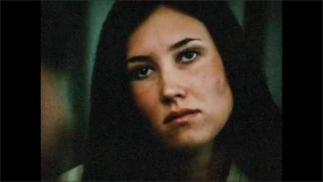 1970s: UNITED STATES: man sits next to slide projector. Close up of lady's face. Production meeting. White end of film reel.