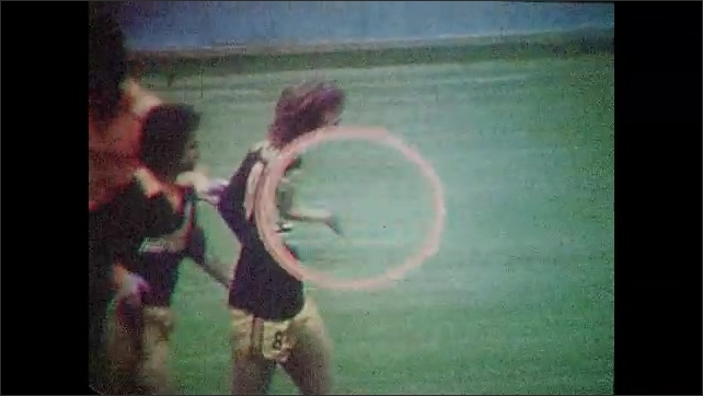 1970s: UNITED STATES: men play soccer on pitch. Player scores goal. Players celebrate goal on pitch. Slow motion of footballer.