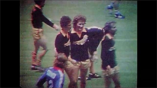 1970s: UNITED STATES: soccer player kicks ball into net. Men celebrate on pitch. Slow motion of goal scored.