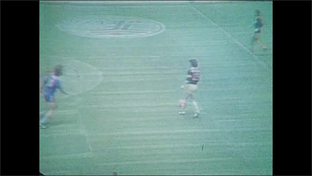 1970s: UNITED STATES: soccer players kick ball on pitch. Men pass ball. People in stands.