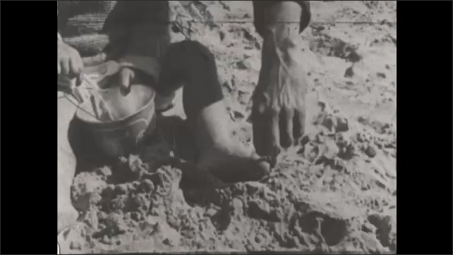1930s: UNITED STATES: toddler on sand. Footsteps in sand. Baby holds stick in toes