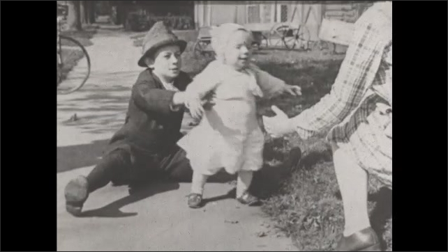 1930s: UNITED STATES: toddler on beach. Lady sits on floor. Toddler learns to walk. Baby in shoes. Kicking legs