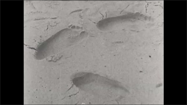 1930s: UNITED STATES: footsteps in sand. Hand points to sand. Young couple on beach