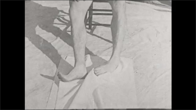 1930s: UNITED STATES: lady sits on chair. Lady with flat feet. Close up of feet