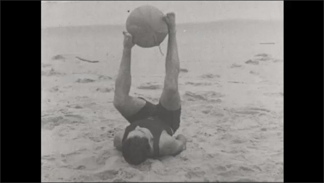 1930s: UNITED STATES: man rotates large ball with soles of feet. Man lies on beach