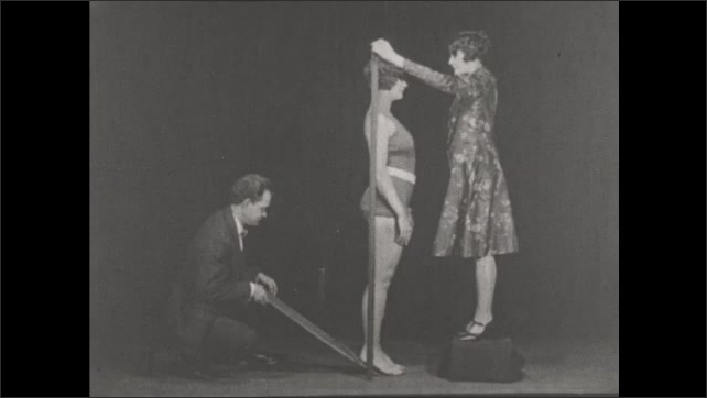 1930s: UNITED STATES: lady stands up straight. Man tilts lady forward. Effect of high heels on posture. Tilted base of spine. Incorrect posture.