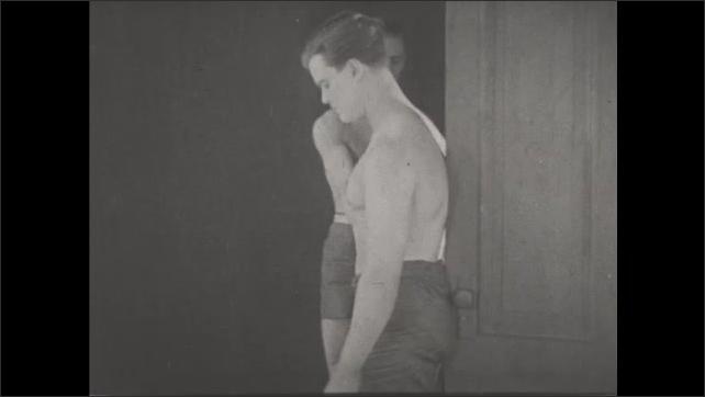 1930s: UNITED STATES: Man stands against door. Straight line postural test against door