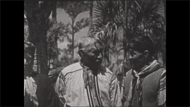 1930s: Seminole Indians stand in palm forest and talk.