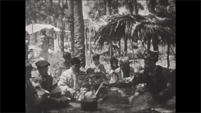 1930s: Seminole Indian tribe sit near fire and eat stew from bowls and ladles.