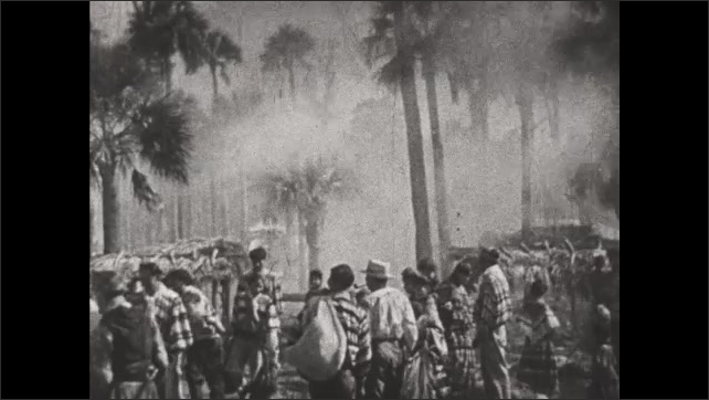 1930s: Seminole Indians gather belongings and move away from smoke and fire.