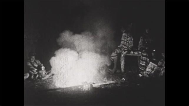1930s: Seminole Indians sit around campfire at night.