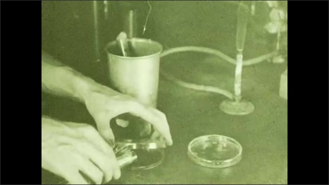 1930s: Man lights cotton ball in beaker on fire, puts of fire, removes cotton ball, pours liquid from beaker into petri dish, moves dish around.