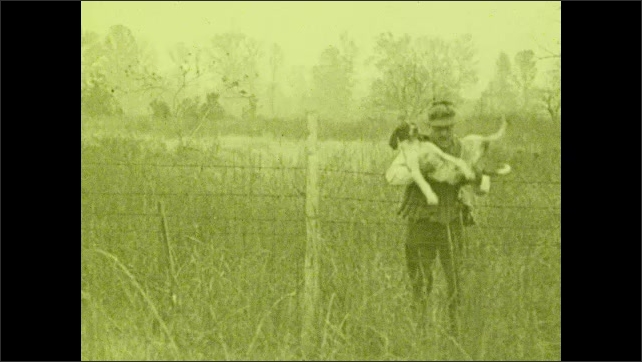 1930s: A man passes a rifle through a wire fence, holds his dog and puts it on the other side of the fence, he climbs the fence, takes his rifle and walks away.