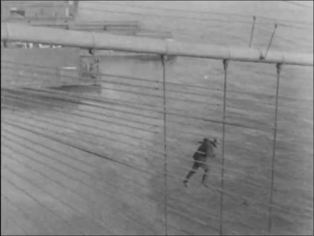 1930s: Man walks in matrix of cables of bridge. Man walks on cables as buses on bridge drive below. Man climbs through high bridge cables. Cars pass below on bridge as man balances in cables.