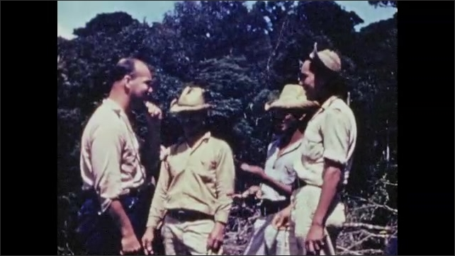 1940s: Men stand and talk.  Men look at slingshots.
