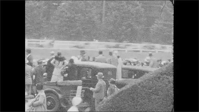 1930s: Jockeys race horses around track. People watch horses race.