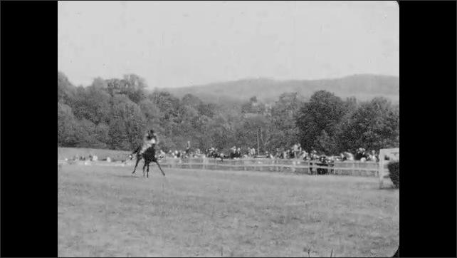 1930s: Jockeys race horses down track, people watch. Horses, jockeys and people mill about field.