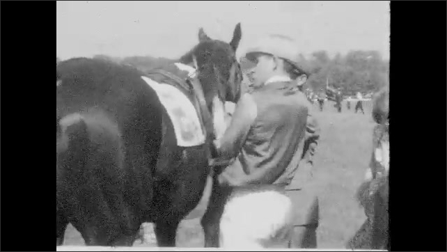 1930s: Jockey rides up to stands on horse, waves to people, dismounts, unsaddles horse. Men and women sit in car, talk.