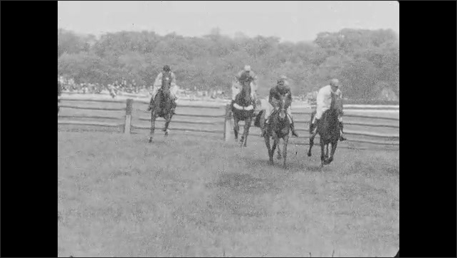 1930s: Jockeys ride horses down track, jump over fence. People watch horse race.