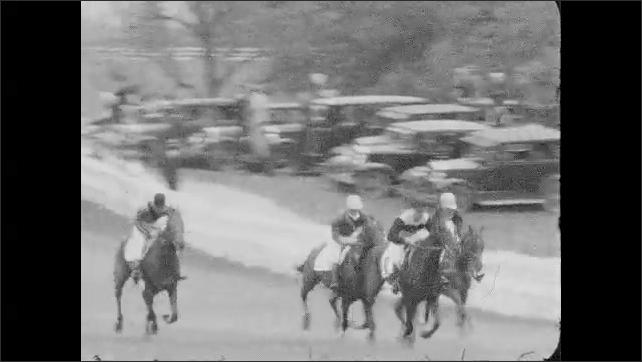 1930s: Jockeys race horses down track, jump over hedge.