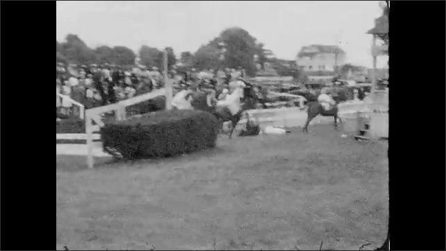 1930s: Jockeys race horses down track, jump over hedge. Horse stumbles, rider falls off horse, people run onto track, help jockey off track.