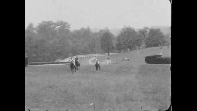 1930s: Jockeys race horses around track, people stand along fences and watch.