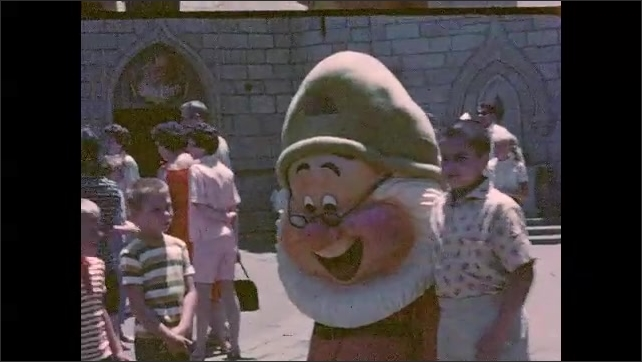 1950s: Young boy standing in front of crowd at Disneyland. Young boys pose with costumed character of one of the Seven dwarves (Doc). Sleeping Beauty Castle. Crowd at Disney pirate ship (Jolly Roger).