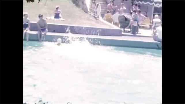 1950s: Group of men and women practice golf swings. Capped women dive into swimming pool and swim. Men and women sit at edge of pool. Legs kicking at edge of pool. Woman dives into pool, swims.