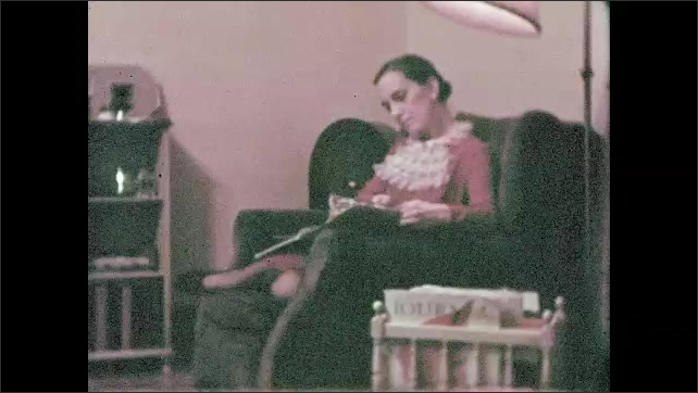1950s: Woman closes refrigerator. Oven and range in kitchen. Bathroom sink. Woman sitting in chair reading book or magazine. Woman walks across room, picks up magazine from radiator and sits on couch.