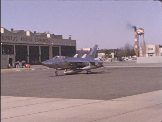 1970s: U.S. Air Force F-105 aircraft drives slowly past Repuublic Aviation Corporation building.