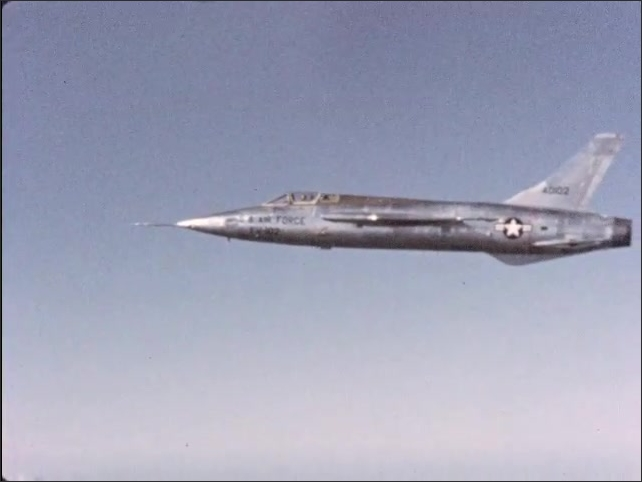 1970s: U.S. Air Force FH-102 aircraft flies to the left.