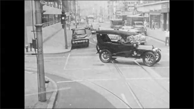 1950s: Ticker tape parade.  Antique cars drive down street.