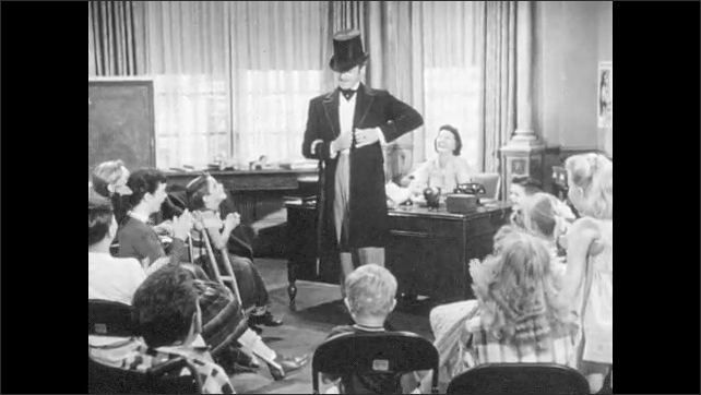 1950s: Man speaks to group of children.  Actor changes costume.  Woman sits at desk.