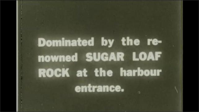 Rio de Janeiro 1930s: traffic near coastal path. Mountain on horizon. Sugar Loaf rock at harbor entrance.