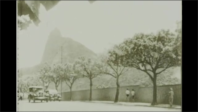 Rio de Janeiro 1930s: Corcovado. Hunchback shaped summit. Colossal statue of Christ. People walk under trees by street. Cars on street