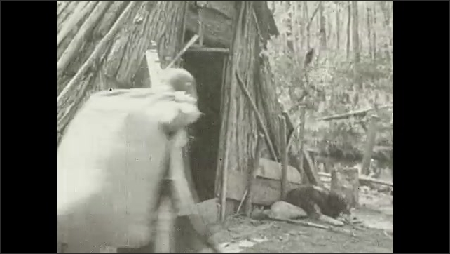 1930s: Village.  Person carries load into shack.  Man smokes and waits outside.