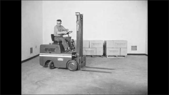 1960s: UNITED STATES: close up of foot on accelerator. Front wheel on fork truck. Rear wheel on fork truck. Man drives fork truck in reverse. Standard fork truck levers