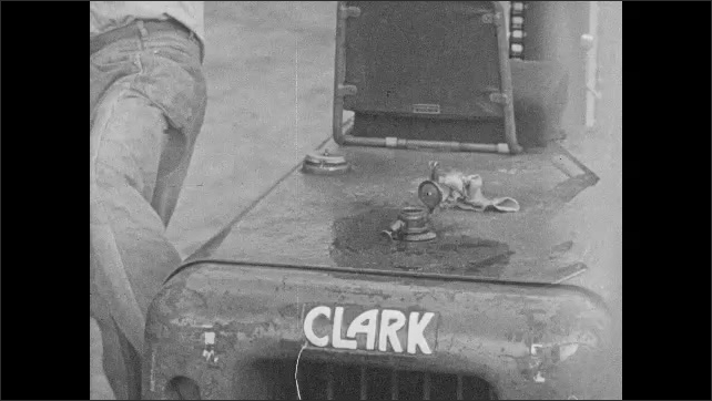 1960s: UNITED STATES: men talk by fork truck. Man smokes by machine. Man wipes up spilled gas. Man wipes hands with cloth. Clark logo on fork truck.