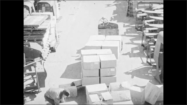 1960s: UNITED STATES: boxes on ground. Boxes fall from tractor on down grade. Man picks up boxes. Hand shifts to slow speed