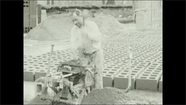 1930s: Man shovels cement into machine, presses it down, clears the excess on the top, moves the machine's lever, it makes a block and takes the block on the ground next to several rows of blocks.