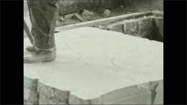 """1930s: Mechanical saw cuts a stone in the middle. Man marks a circle on stone with a big compass. Intertitle """"Grindstones contain sharp-edged grains of sand"""". Hands hammer on the stone surface."""